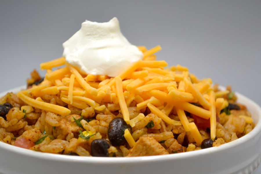 a white bowl heaped with mexican fried rice and topped with orange cheddar cheese and a dollop of white sour cream