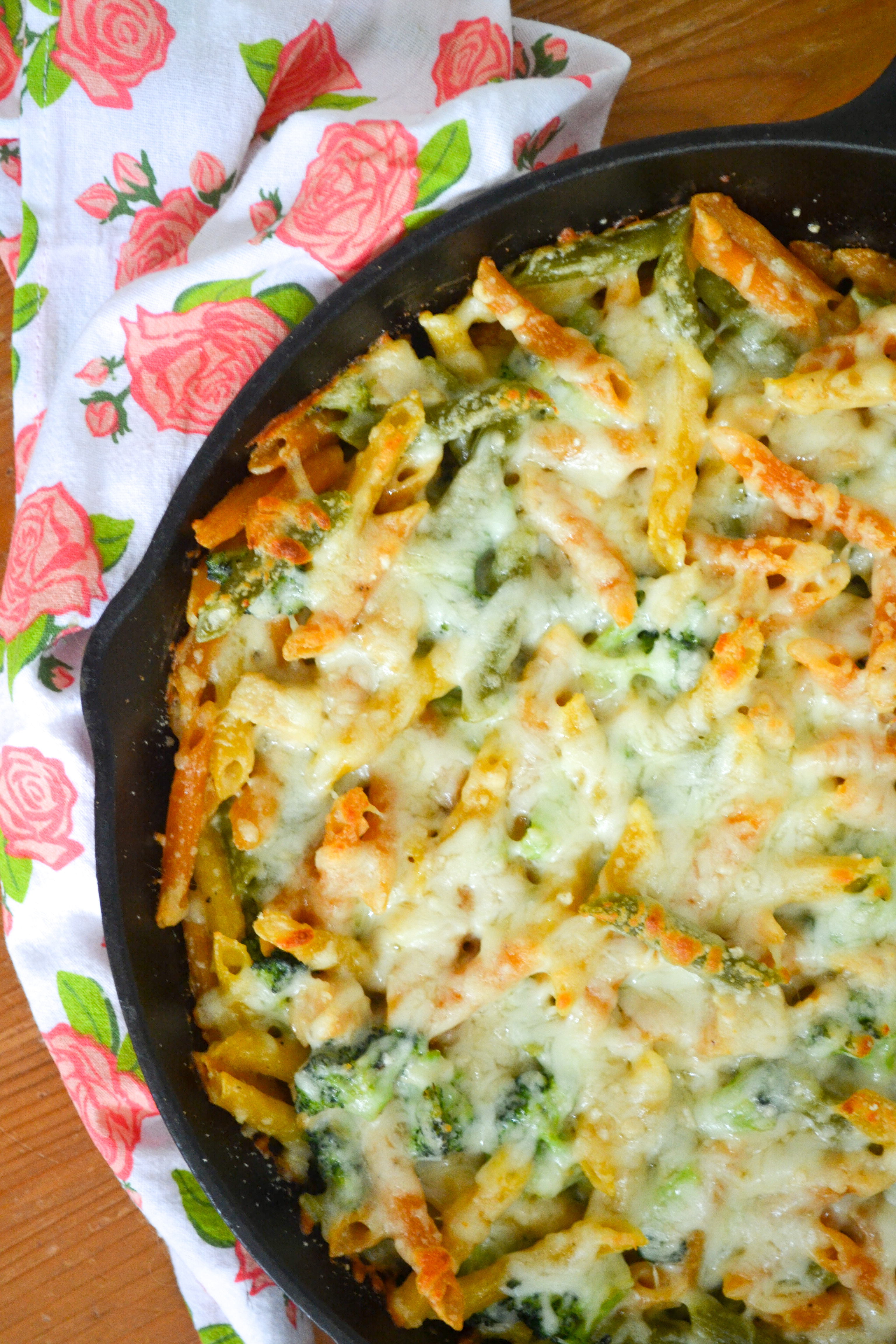 a cast iron pan with healthy chicken alfredo bake on a rose covered tea towel
