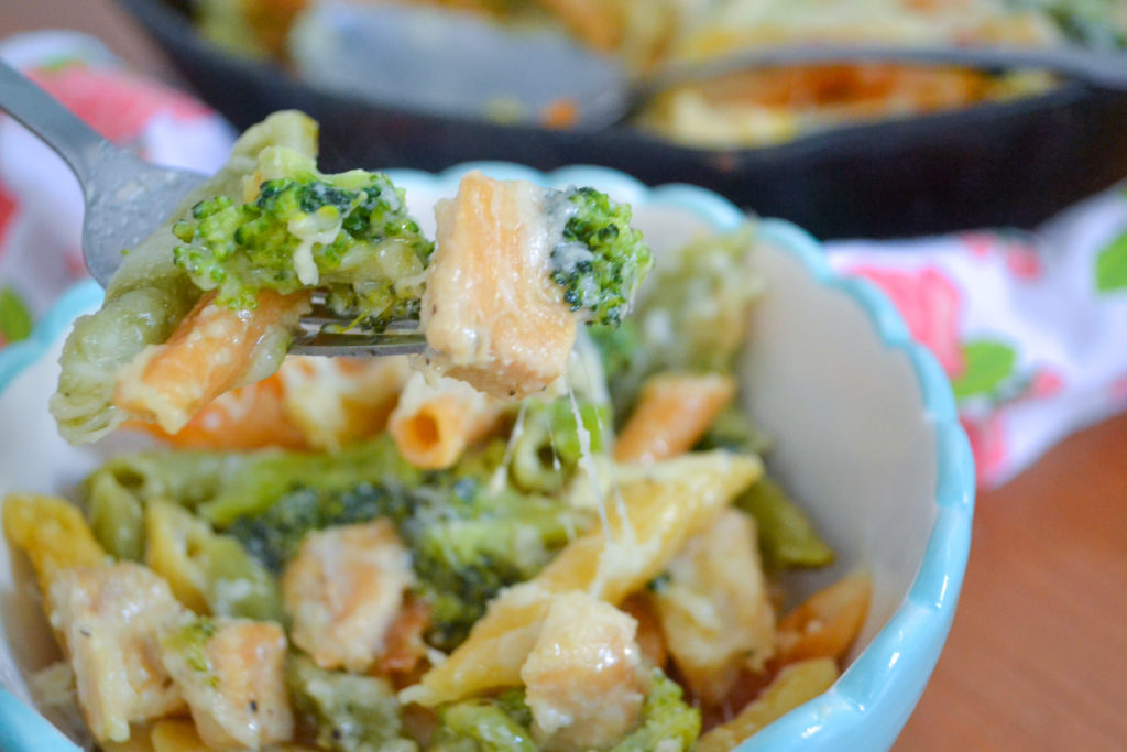 a fork holding noodles with chicken and broccoli for healthy chicken alfredo bake