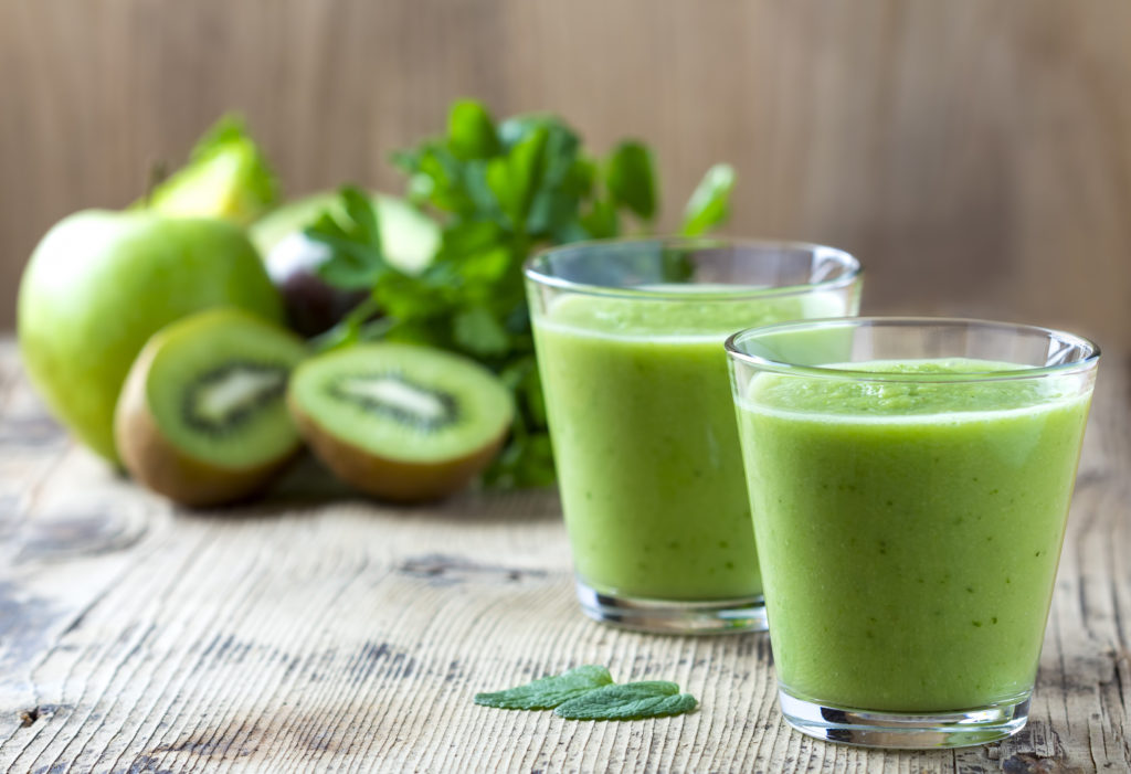 Green veggie smoothies in 2 glassed on a wooden surface with parsley, apples, and kiwi in the background