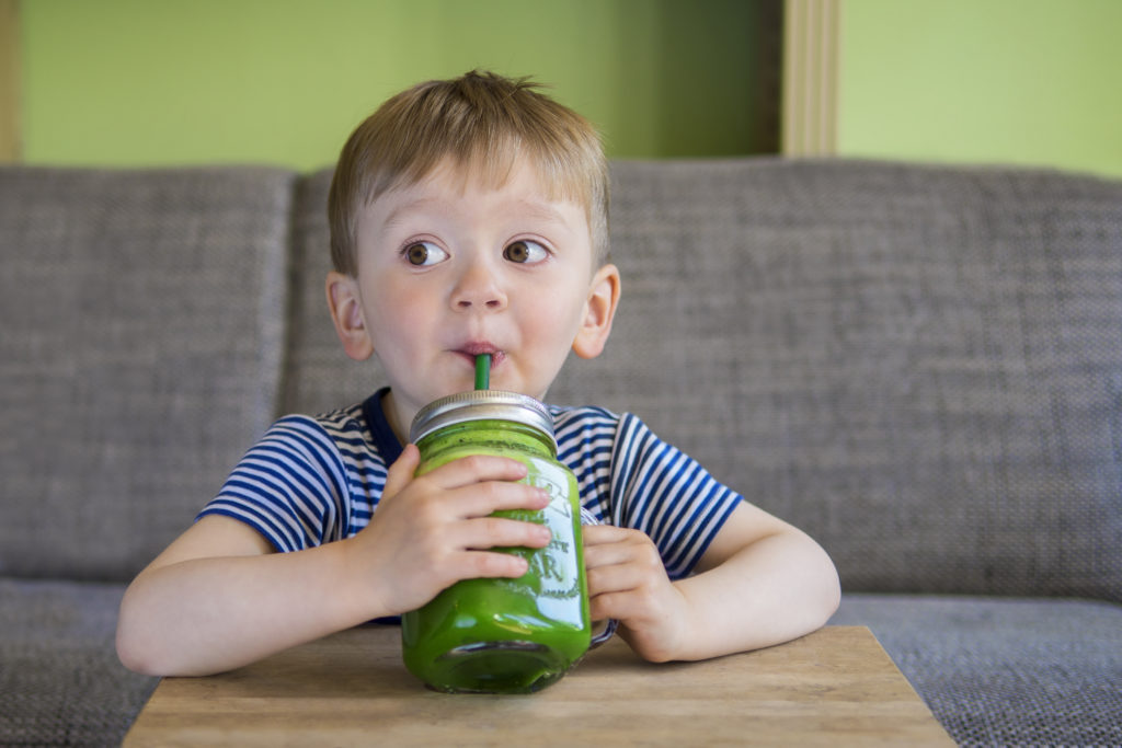 a boy in a striped shirt drinking a green veggie smoothie from a lidded glass mason jar with a green straw.