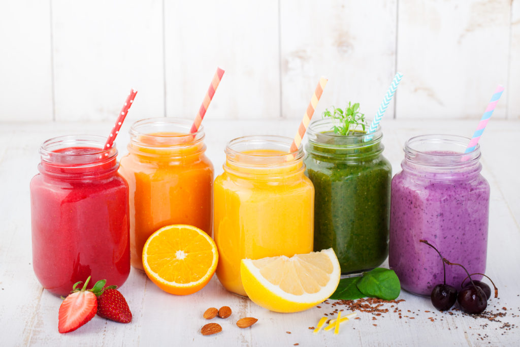 A rainbow of 5 veggie smoothies in square glass mason jars with colored paper on a marbles tile background with colorful fruits in front of them.