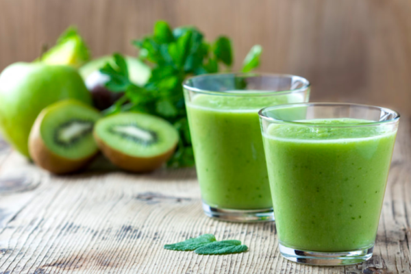 Green veggie smoothies in 2 glasses on a wooden surface with parsley, apples, and kiwi in the background