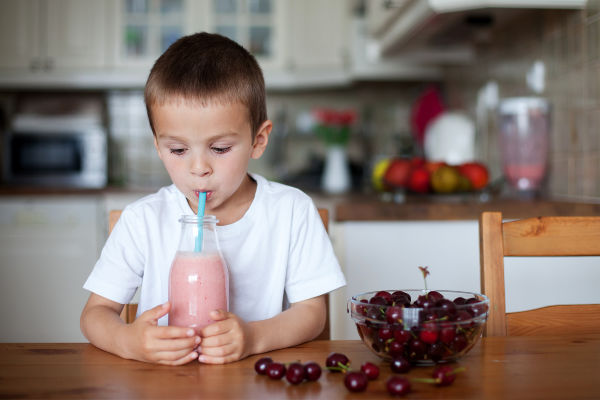 A little boy in a white tee shirt drinking a pink veggie smoothie from a blue straw at a wooden table in a kitchen next to a bowl of black cherries