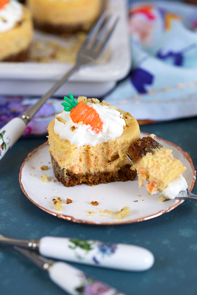 a kid friendly carrot recipe of a mini carrot cake cheese cake with a bite taken out on an antique white plate