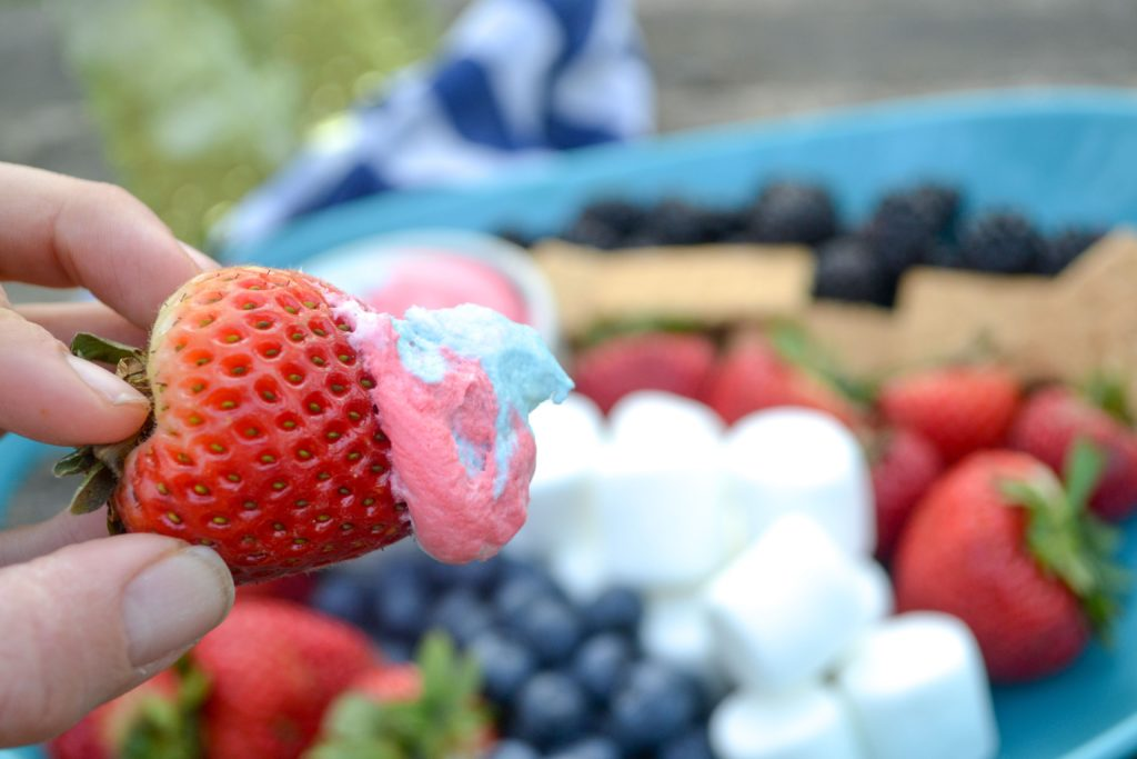 a strawberry dipped in red white and blue fruit dip in front of a patriotic fruit platter outside