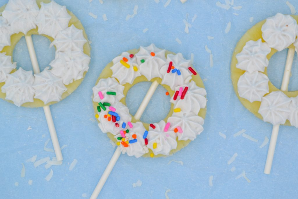 three pina colada pineapple popsicles with coconut cream and rainbow sprinkles, with a blue back ground on top of parchment paper