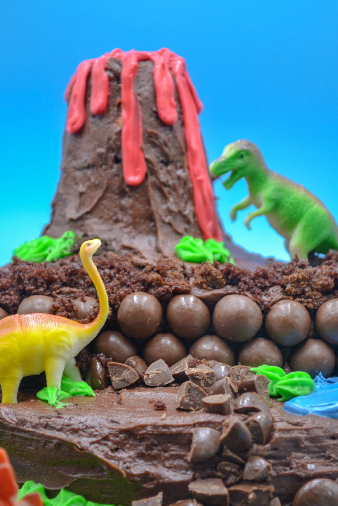 a chocolate dinosaur birthday cake with a toy brontosaurus and trex with a chocolate volcano and chocolate 'rocks'