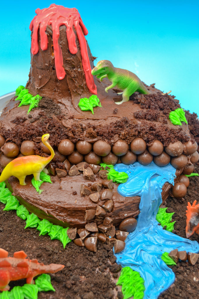 a dinosaur birthday cake with chocolate frosting, a volcano, a blue frosting waterfall, and toy dinosaurs on a blue background