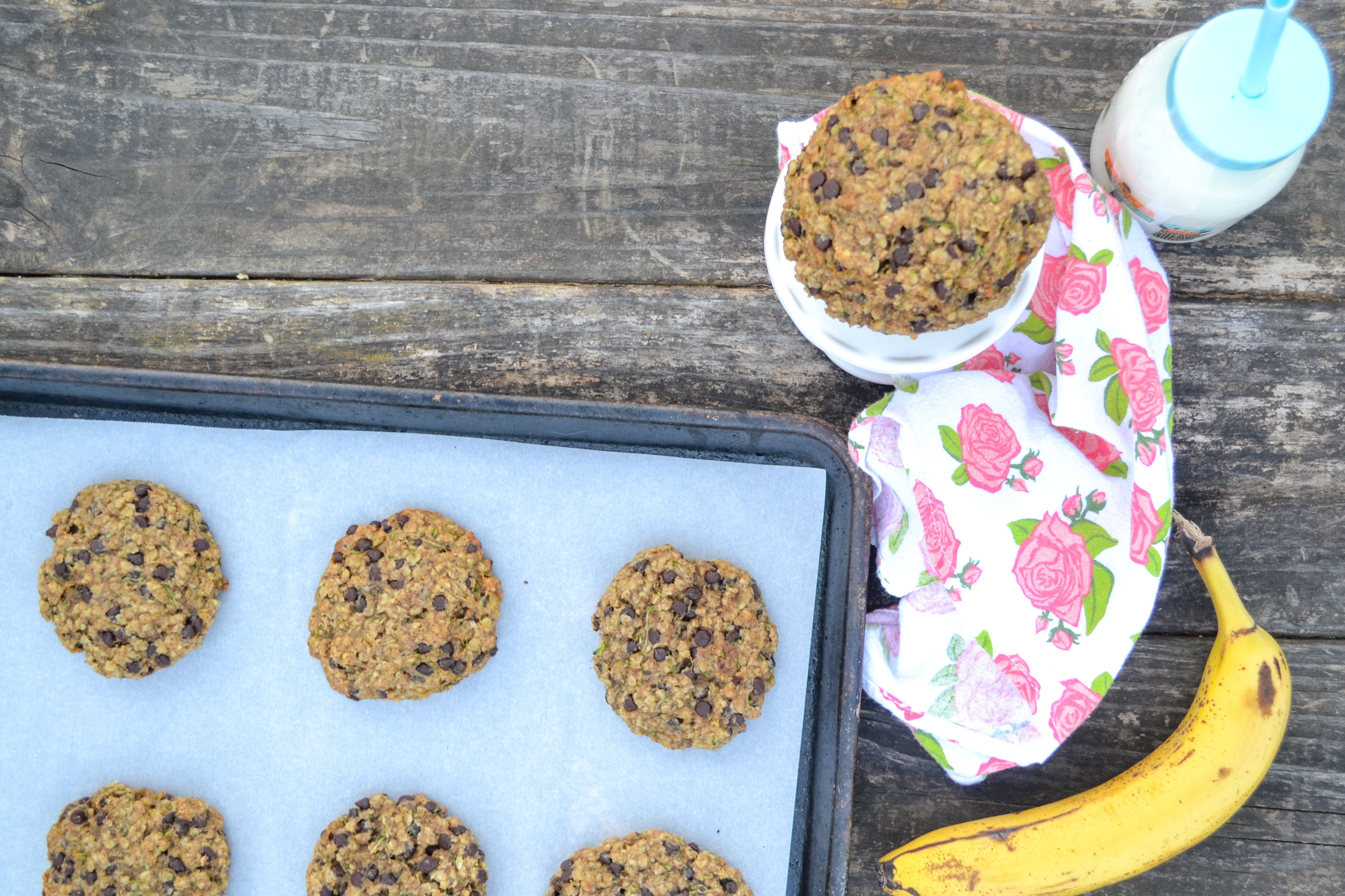 a cookie sheet with veggie cookies laid on it, with a rose towel, cup of milk, and a yellow banana all laying on a wooden table.