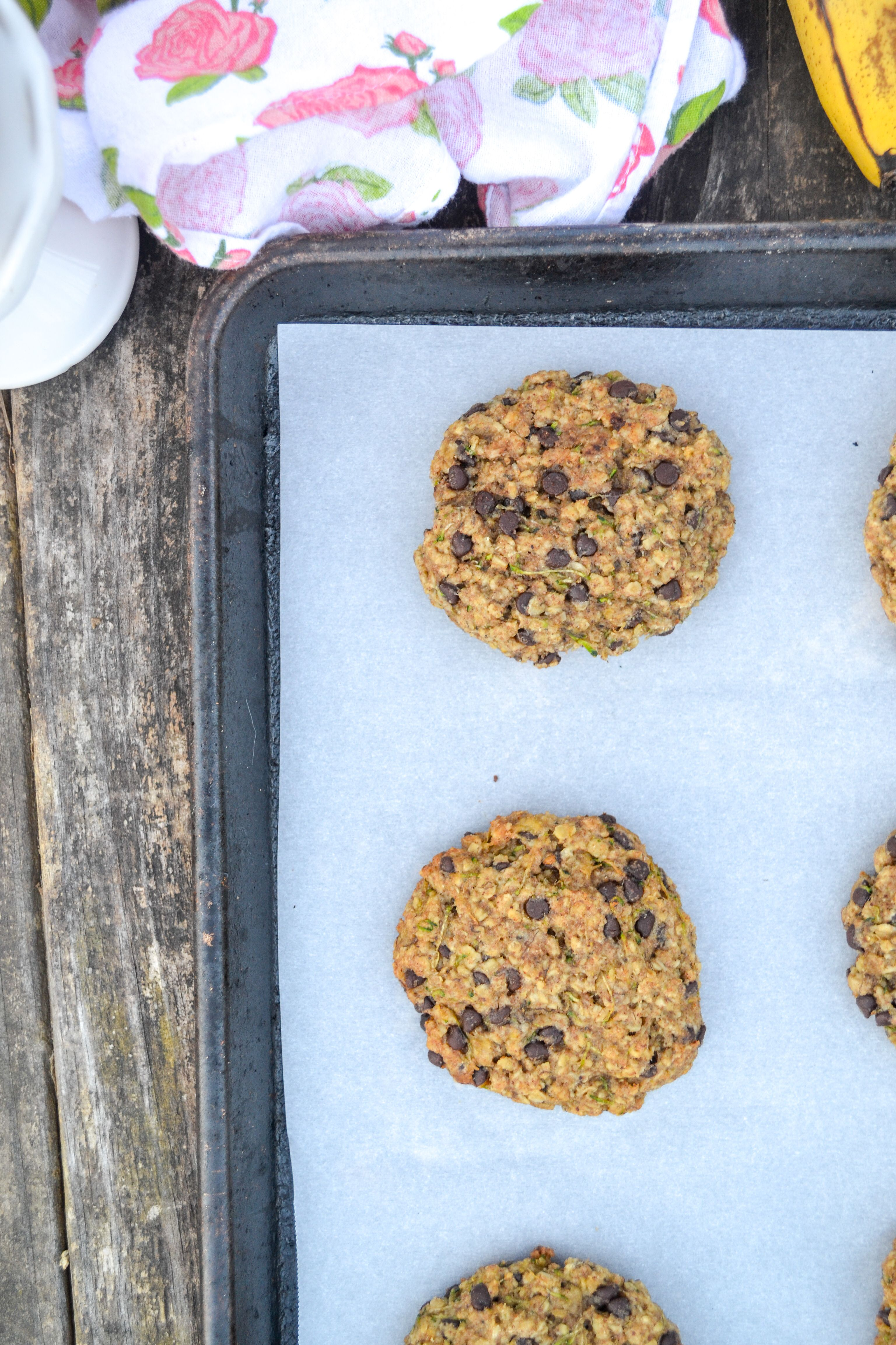 a cookie sheet with oatmeal zucchini veggie cookies with a rose towel on a large wooden table
