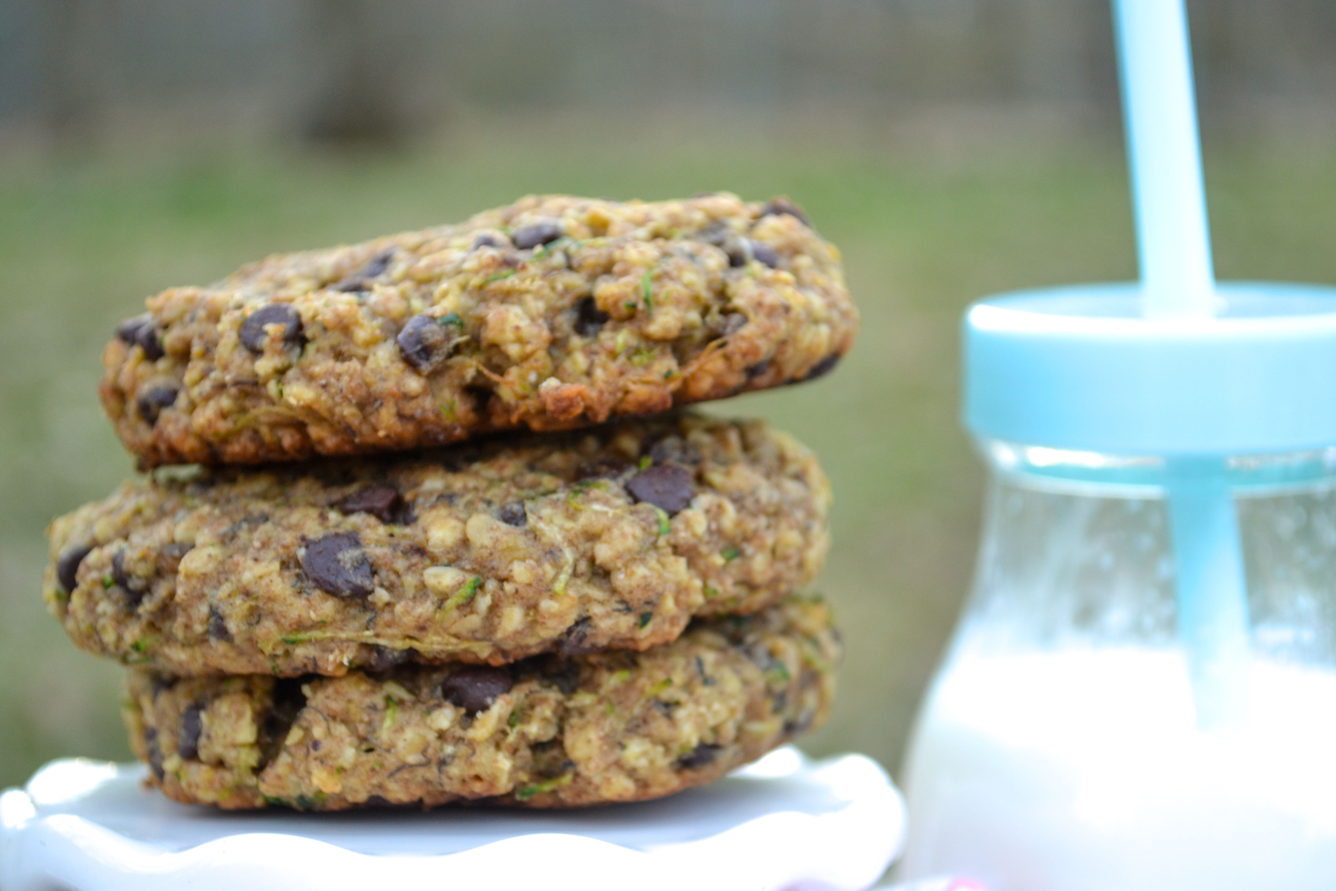 a stack of oatmeal zucchini cookies on a white stand with a glass of milk in the background