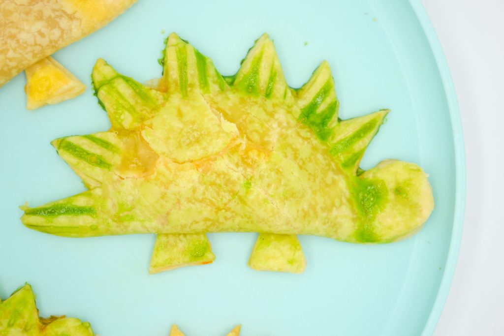 green dinosaur homemade pizza pocket on a blue plate