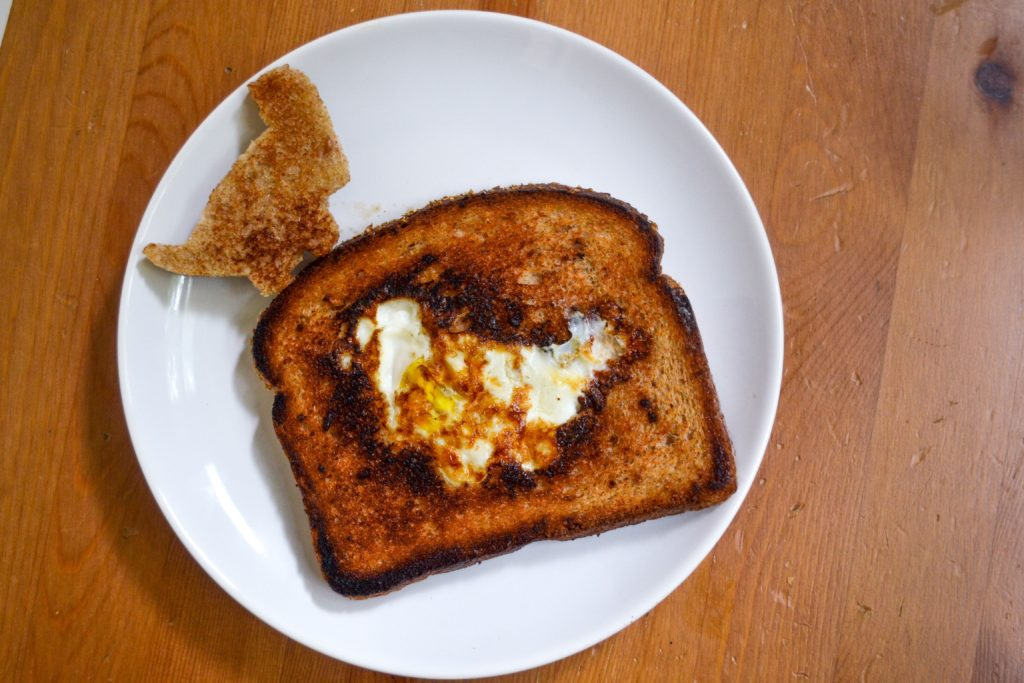 an egg in a hole on a white plate on a wood table