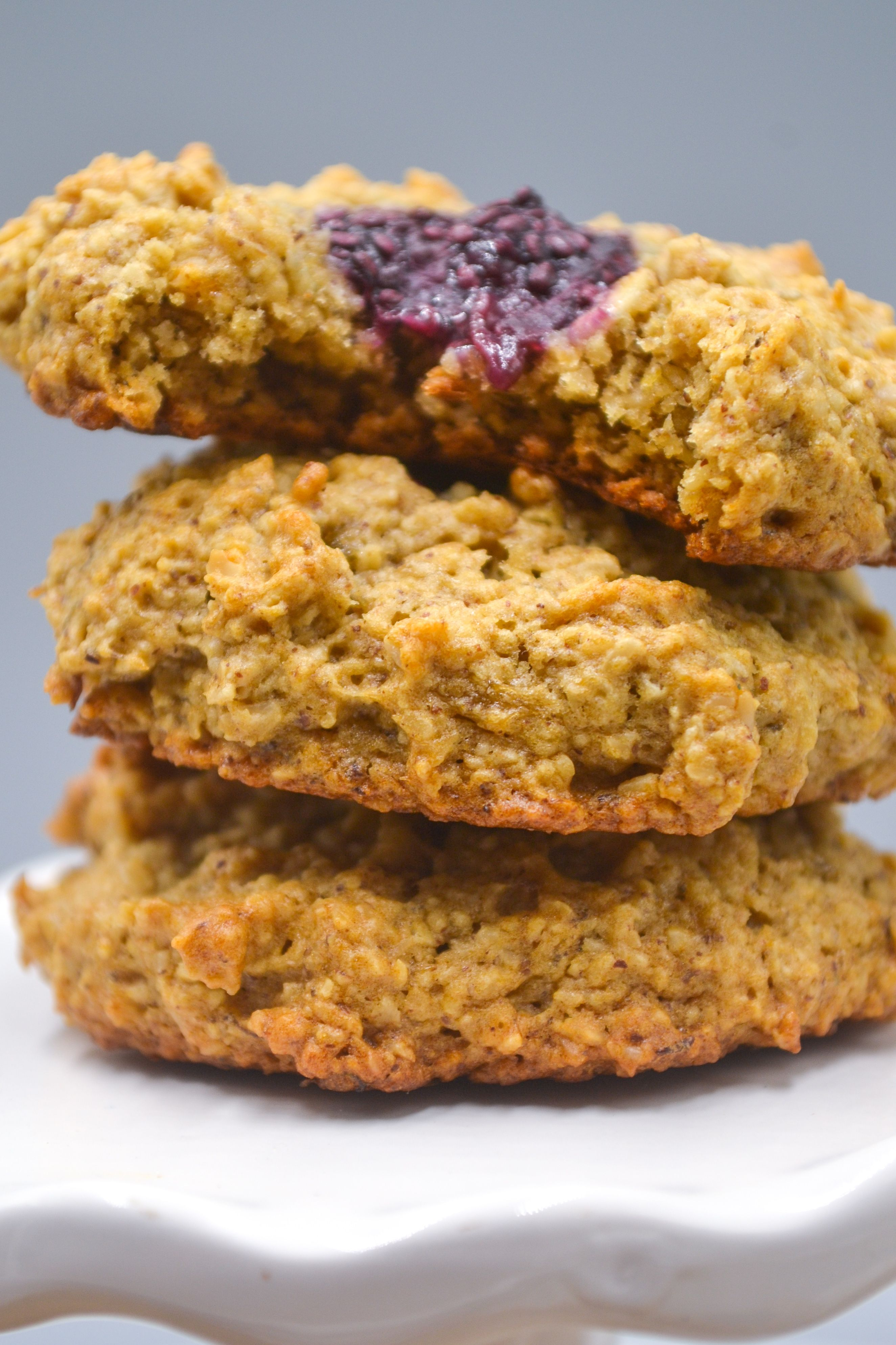 three oatmeal thumbprint cookies with chia seed jam stacked on top of each other on a white stand