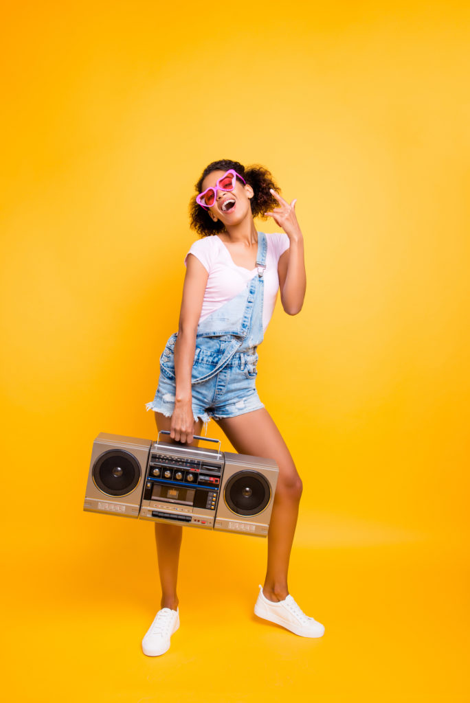 a bright yellow background with a young girl holding a boom box and listening to dance music for kids