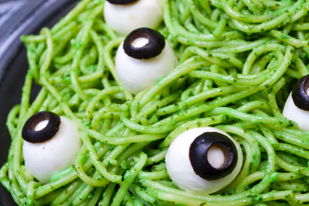 bright green spaghetti noodles covered in veggie pesto and topped with mozzarella eyeballs