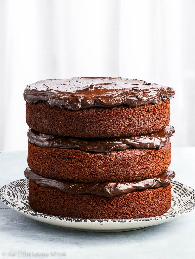 a 3 layer paleo chocolate cake on a white and grey patterned plate - this cake is both healthy and delicious!