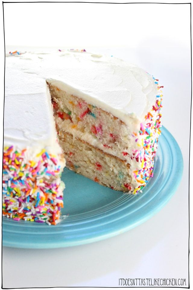 a white funfetti healthy cake recipe on a blue plate with tons of rainbow sprinkles and a large slice taken out of it.