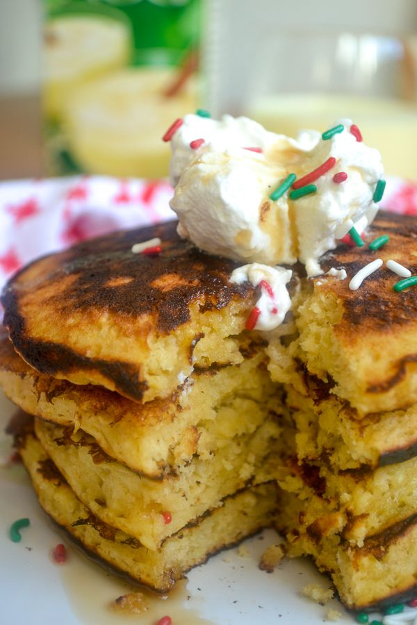A cut stack of eggnog pancakes topped with homemade eggnog whipped cream, syrup, and sprinkles on a white plate