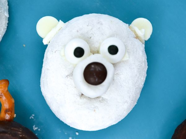 powdered sugar donut with chocolate chips and candy eyes to look like a polar bear