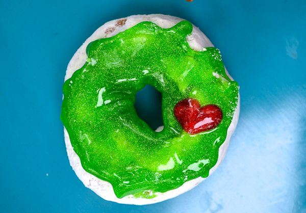 red and green decorating gel covering a donut to make a grinch heart