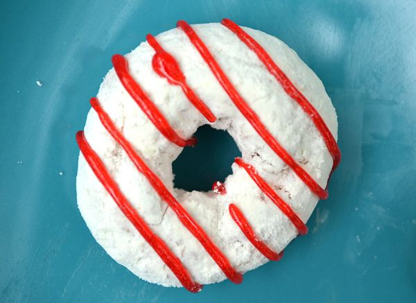 A white powdered sugar donut with red striped to look like a candy cane donut on a blue plate