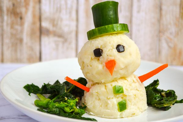 two balls of mashed potatoes stacked and topped with vegetables to make a mashed potato snowman