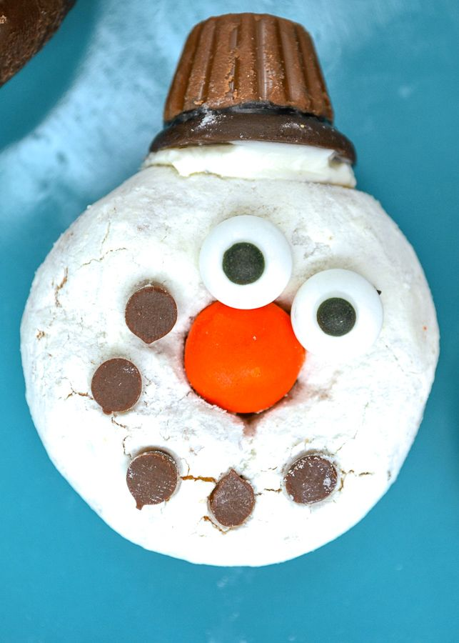 a white powdered sugar donut with a mini PB cup made to look like a snowman donut
