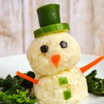 a snowman made of vegetables and mashed potatoes with broccoli rabe on a white plate