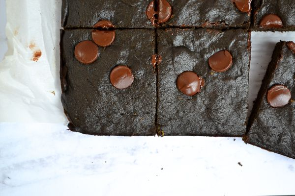 a horizontal image of spinach brownies removed from the pan and on parchment paper, cut with one removed.