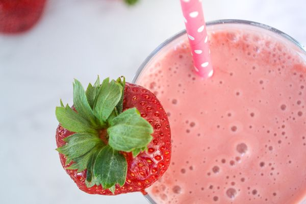 an overhead shot of a strawberry smoothie in a class with a straw with a berry on the side