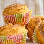 sweet potato muffins in pink and green swirled cupcake wrappers stacked on parchment with a light wood background