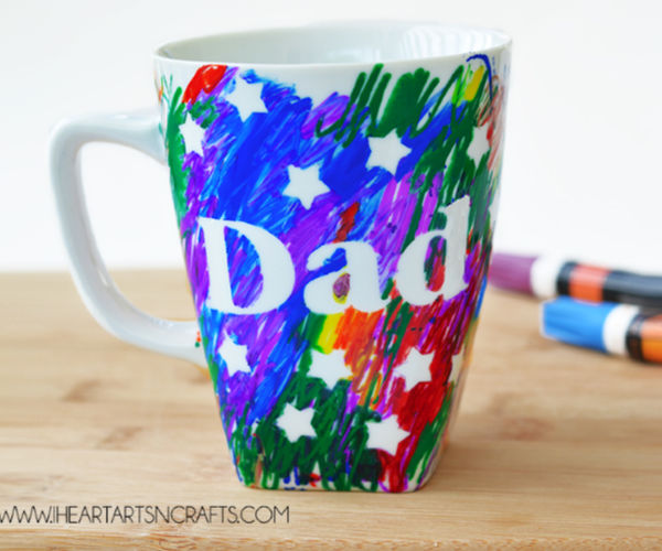 "a colorful mug colored in by children as a gift for grandparents with ""dad"" on it."