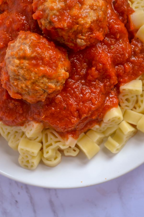 veggie sauce piled on top of ABC noodles with meatballs on a white plate and a marble counter