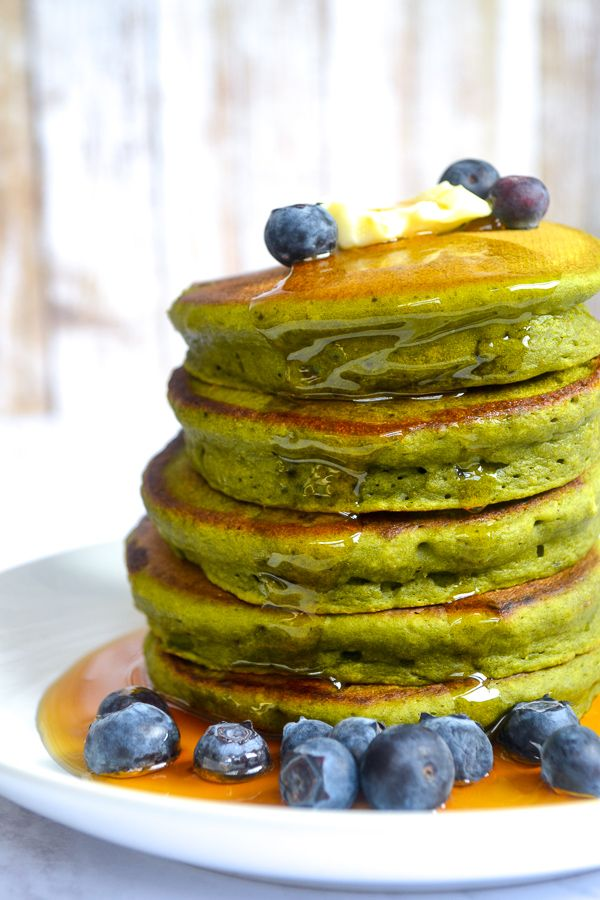 a stack of bright green spinach pancakes on a white plate in a puddle of maple syrup with blue berries