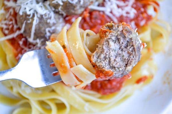 a fork holding fettucini, tomato sauce, and a bitten zucchini meatball
