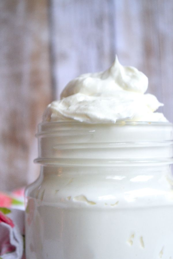 a mason jar filled with sugar free frosting in front of a wooden wall