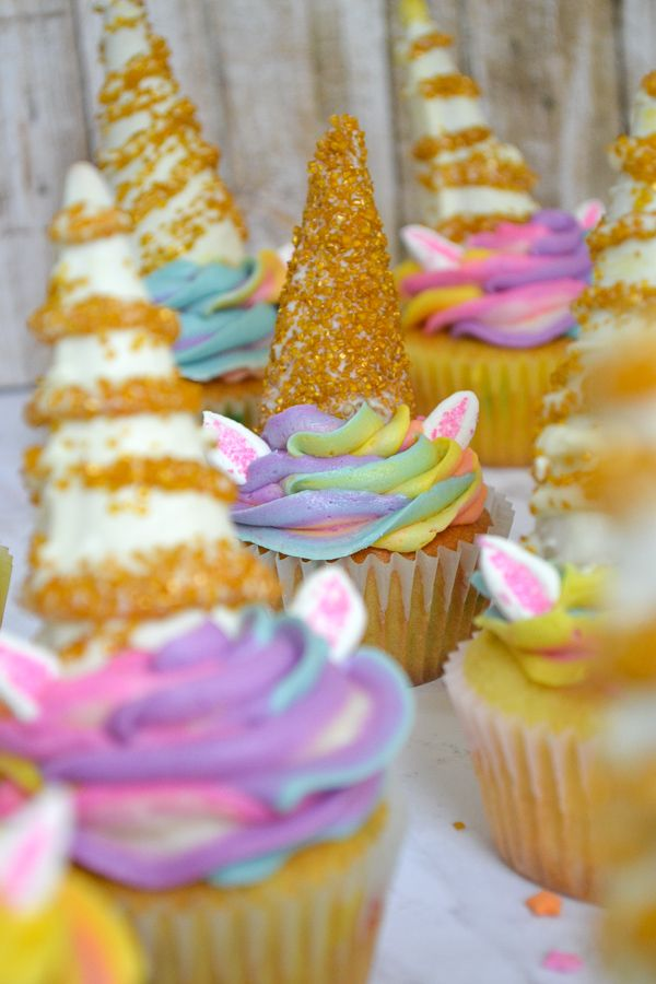 unicorn cupcakes out of focus with one cupcake in focus. The cupcake has a fully gold sprinkle unicorn horn.
