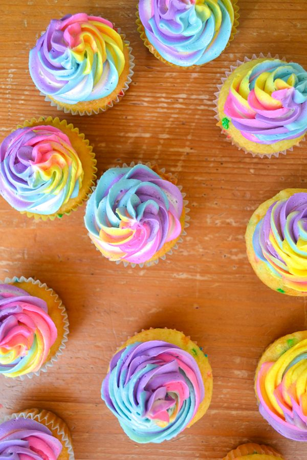 sprinkle cupcakes over head, piped with rainbow unicorn frosting on a wooden table.
