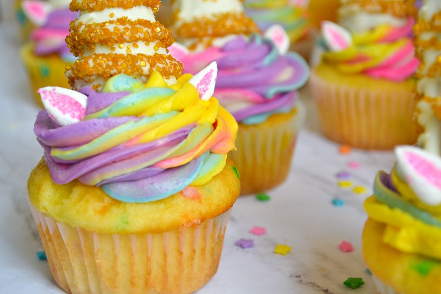 a horizonetal, close up image of a cupcake topped with piped rainbow frosting, marshmallow ears, and an edible unicorn horn.