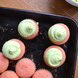 pink mini cupcakes on a dark weathered cookie sheet with dollops of green frosting