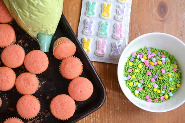 a cookie sheet with mini pink cupcakes, green frosting in a piping bag, a white bowl with green sprinkles and sugar bunny decorations