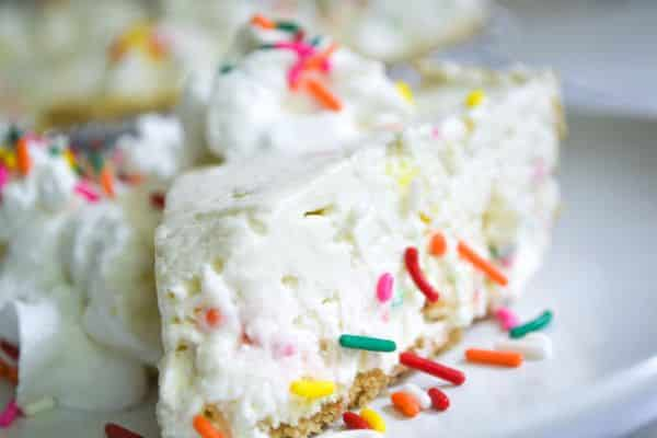 a slice of funfetti cheesecake topped with whipped cream and rainbow sprinkles on a white plate.
