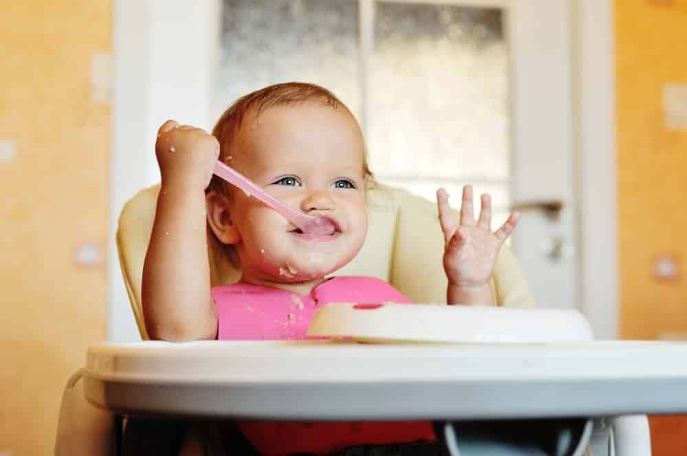 a baby eating oatmeal using baby led weaning on a preloaded spoon
