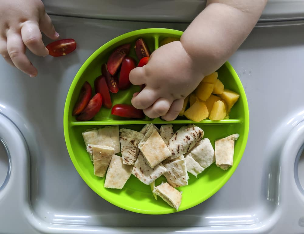a photo of a  baby hand eating fruit, tomatoes and pita cut for baby led weaning