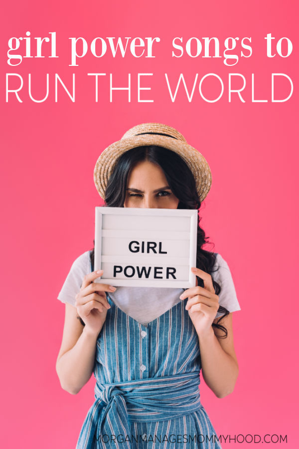a woman holing a letterboard that reads girl power on a brihgt pick backdrop