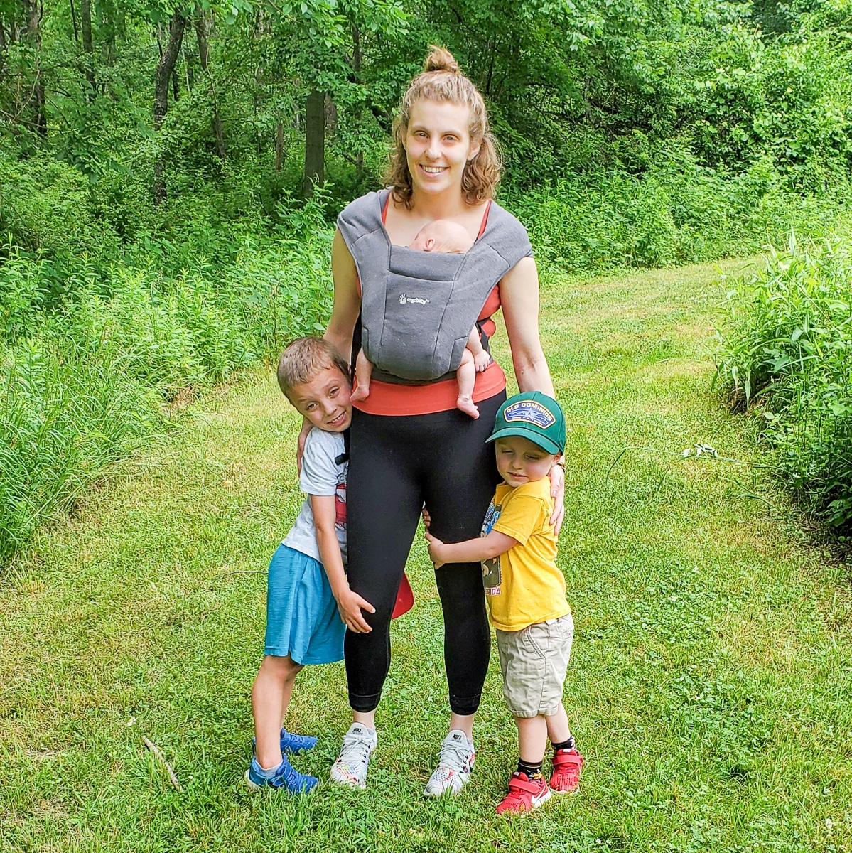 a woman wearing an ergo embrace in the woods with 2 other kids in the photo