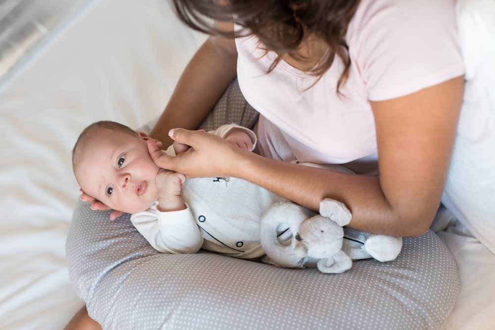 a mom holding a baby on a nursing pillow in a bed.