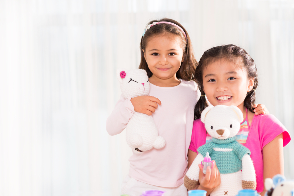 two little girls holding knit stuffed animals.